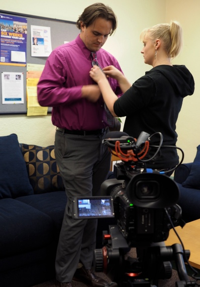 Emilie Johnson adjusts a microphone on journalist J. David McSwane before an interview in the Armory on CU's main campus on Friday, January 23, 2015. (Photo/Roxann Elliott)